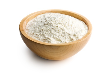 flour in wooden bowl on white background