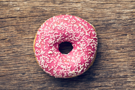 pink donut on old wooden background