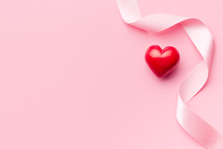 Photo pour pink ribbon with red heart on pink background - image libre de droit