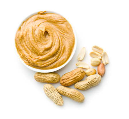 Creamy peanut butter and peanuts  isolated on white background. Spreads peanut butter in the bowl.