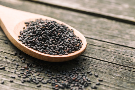 Black sesame seeds. Healthy sesame seeds in spoon on wooden table.