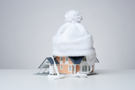 Baby cap isolate model of the house against heat leak - house insulation concept. Gray background.