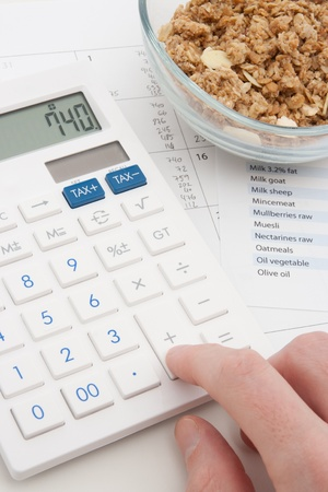 Healthy eating concept - man calculate his daily nutrition intake  Muesli in glass bowl, calculator, calendar and nutrition chart