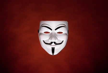 Studio shot of an Anonymous face mask, known as Guy Fawkes Mask from the movie V for Vendetta on dark red background