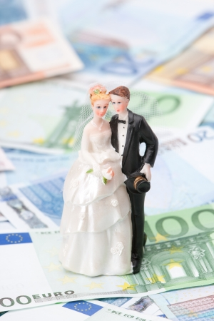 Wedding expense concept - wedding figurines  bride and groom  and money