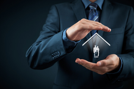 Foto de Insurance concept of family life and property insurance, family services, family policy and supporting families concepts. Businessman with protective gesture and silhouette representing young family and house. - Imagen libre de derechos