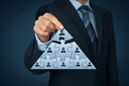 Foto de CEO, leadership and corporate hierarchy concept - recruiter complete team represented by puzzle in pyramid scheme by one leader person (CEO). - Imagen libre de derechos
