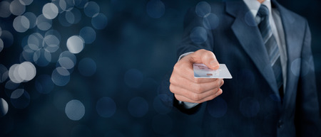 Photo pour Businessman in business suit pay by credit card. Wide banner composition with bokeh in background. - image libre de droit
