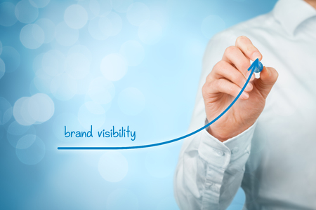 Brand visibility improvement concept. Brand manager (marketing specialist) draw growing graph with text brand visibility.