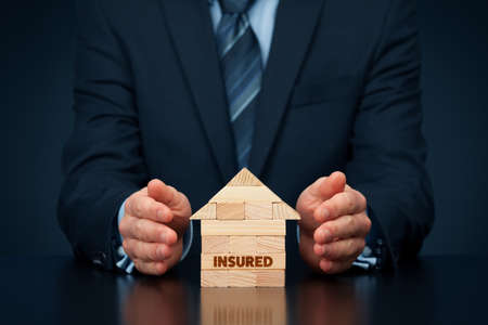 Photo pour Property (family house) insurance protection concept. Insurance agent protect by hand model of the house with text insured, made from wooden pieces. - image libre de droit