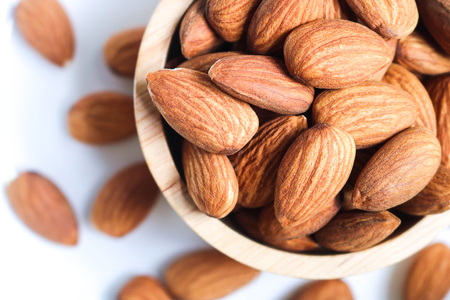 Foto de Almond nuts in wooden bowl on white background. Almonds are healthiest nuts and one of the best brain foods. - Imagen libre de derechos