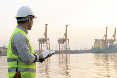 Photo pour Engineering is using the tablet. To check the details and use in the work order for flexibility Cargo handling. The background is the shipping port. - image libre de droit