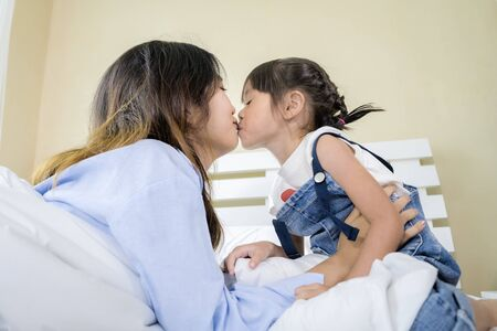 Photo pour Asian women, pretty face, her sister and her sister ties a lot, show their love by kissing each other, they were sitting on the bed. - image libre de droit