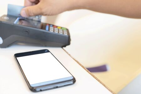 Credit card payment, buy and sell products & service, Hand Swiping Credit Card. Moment of payment with a credit card through terminal, Smartphone that is placed in the text.