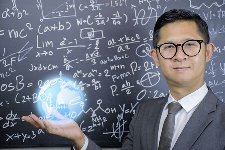 Photo for STEM concept.Mathematics teachers wear glasses, wear suits, look dignified, trustworthy.He opened his hand and had a globe on it.The background is a blackboard with mathematical formulas. - Royalty Free Image
