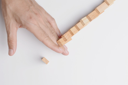 Man hand stop and block domino effect to protect last piece of wood block from collapse. Top view on gray background.
