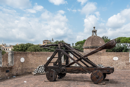 Rome, Italy - August 19, 2016:  Old roman catapult in Castel Sant Angelo a cloudy summer day. The Mausoleum of Hadrian, usually known as Castel Sant'Angelo is a towering cylindrical building in Rome