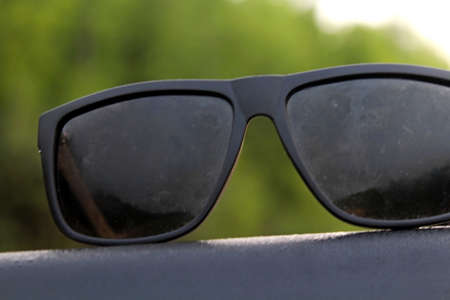 Photo pour Sunglasses on the roof of a car during sunrise against the backdrop of the surrounding nature - image libre de droit