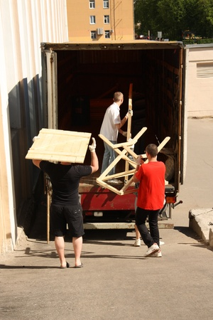 Removal men working with pieces of furniture