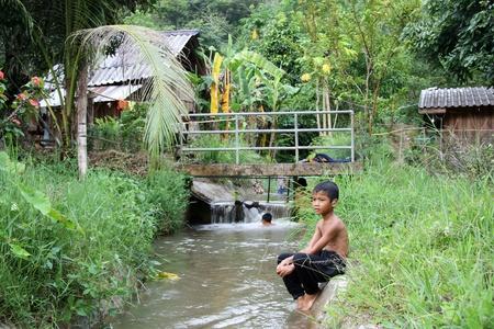 Foto de Thailand rural scenery with a small boy sitting at the bank of river, Pai, Thailand - 01.08.2011 - Imagen libre de derechos