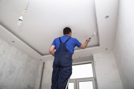 Man worker paints the ceiling inside of the room interior
