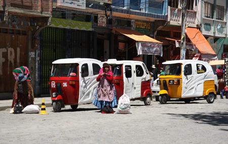 BOLIVIA, COROICO, 27 SEPTEMBER 2013 - Tuk Tuk taxi cars in a row and Bolivian women in a street of Coroico, Bolivia, South America