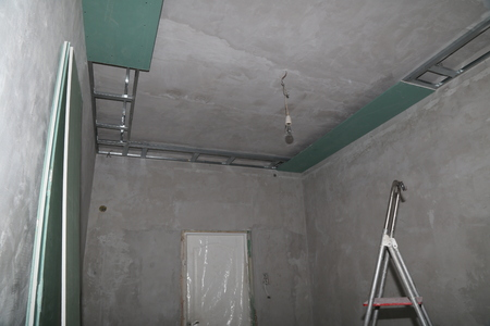 Fixing plaster boards at the ceiling of a house under construction.の写真素材
