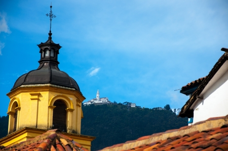 A yellow church in Bogota with Monserrate in the background