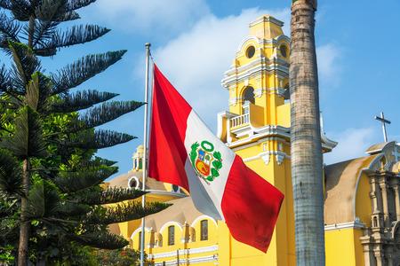 Peruvian flag and yellow church in the Barranco neighborhood in Lima Peru