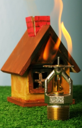 Close up image of fire sprinkler. Fire sprinklers are part of an integrated water piping system designed for life and fire safety. Replica of house on fire added to background.