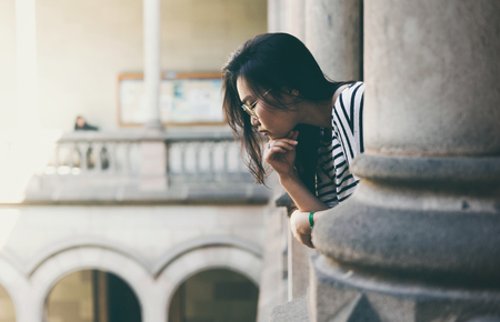 Attractive asian student girl wearing glasses thinking about dream job while standing on the balcony of the old national university. Young freelancer is getting the inspiration while walking old city.