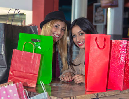 Foto de Two young blonde and brunette friends sitting in a coffee shop after a sales day with many colorful bags with their purchases - Imagen libre de derechos