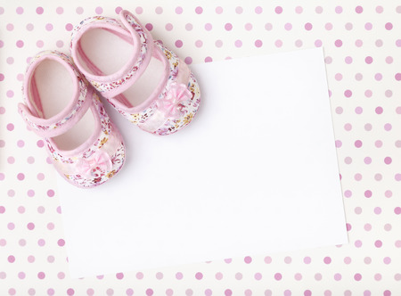 Blank card with baby girl shoes on a pastel pink spotted background.