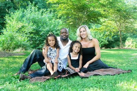 A loving mixed race family enjoying the park