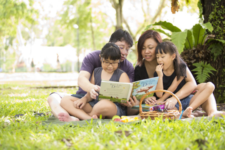Young Asian family reading in park