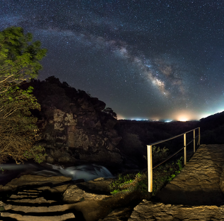 Milky way panorama on a staircase leading to a waterfall
