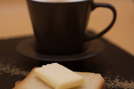 Photo pour White coffee and toast with butter and sugar. Breakfast in black tray on orange background. Cappuccino. - image libre de droit