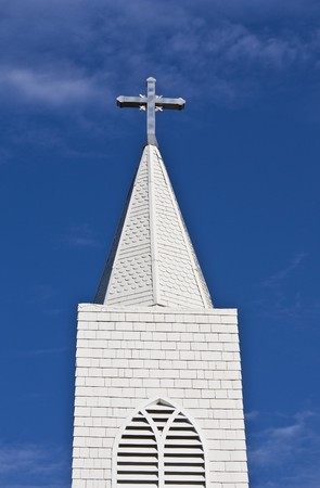 Looking up at a church steeple and cross