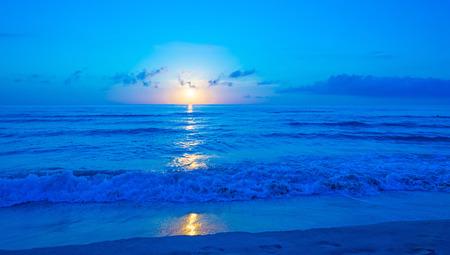 Sunrise over a beach in blue
