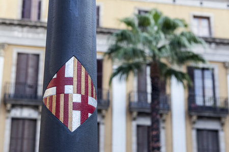 BARCELONA,SPAIN-JANUARY 26,2016: Shield of the city in a streetlight designed by Antoni Gaudi in Plaza Real of Barcelona.