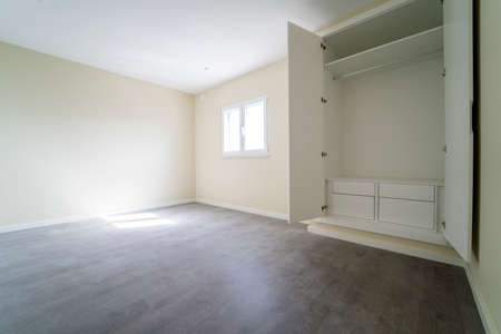 Foto de Empty room with dark wooden floating laminate flooring and wardrobe. House interior, wide bedroom space. Newly recently painted new apartment or house. Wood floor. Real state and property management - Imagen libre de derechos