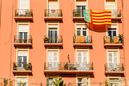 Valencia, Spain - March 16, 2019: Facade of a building with a large Señera, flag of Valencia, hanging from a balcony during the celebration of the Fallas.