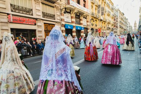 Valencia, Spain - March 17, 2019: Fallera Commission parading down Calle de la Paz, seen from behind, during the Fallas offering.