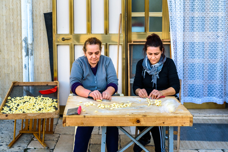 Foto de Bari, Italy - March 8, 2019: Artisan women preparing at the door of their house in the Italian city of Bari the traditional ear-shaped pasta, called orecchiette, made with flour and salt water, and folded in the street. - Imagen libre de derechos
