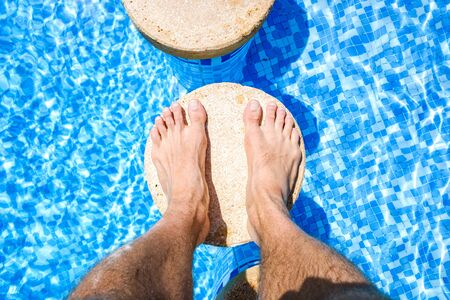 Photo for Feet of a vacationer relaxing in a pool. - Royalty Free Image