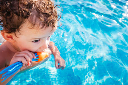 Photo pour Baby girl playing in the pool with a plastic toy in summer in the sun with copy space. - image libre de droit