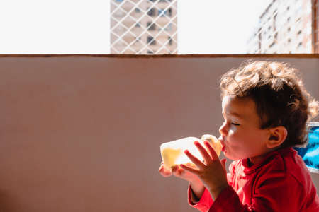 Photo for Baby sitting on the balcony of her house in the sun drinks milk from a bottle by herself. - Royalty Free Image