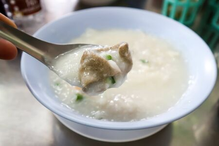 eating rice gruel, rice porridge or congee dish
