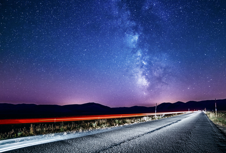 Night sky with milky way and stars. Night road illuminated by car. Light trails