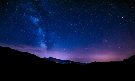 night sky stars milky way blue purple sky in starry night over mountainsの写真素材